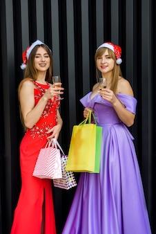 Paar frauen in eleganten kleidern, die auf neujahrsparty feiern und anstoßen