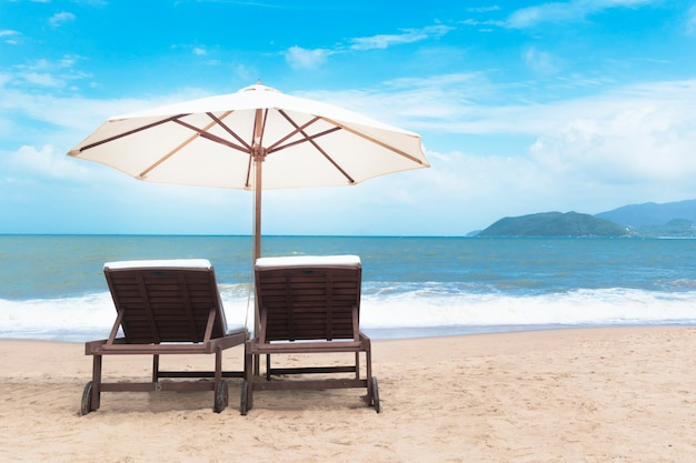 Paar freie sonnenliegen mit sonnenschirm, sonnenschirm am schönen leeren strand nahe meer