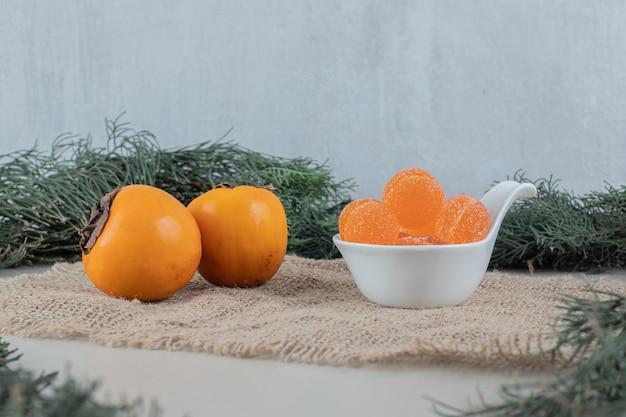 Paar frische kakis mit orangenmarmeladen.