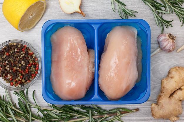 Paar frische rohe hähnchenbrust oder filet in plastikbehälter mit ingwerwurzel, knoblauch, zwiebel, zitrone, pimentpfeffer in glasschüssel und rosmarin auf holzhintergrund. ansicht von oben.