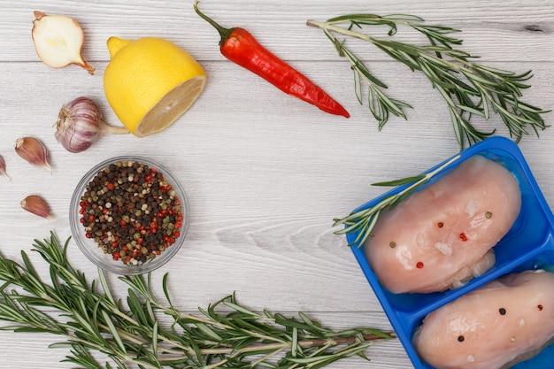 Paar frische rohe hähnchenbrust oder filet in plastikbehälter mit pfefferchili, knoblauch, zwiebel, zitrone, pimentpfeffer in glasschüssel und rosmarin auf holzhintergrund. ansicht von oben.