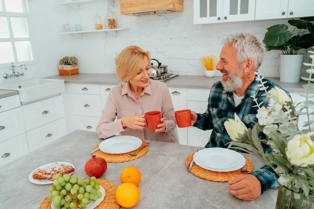 Paar frühstückt zu hause mit kaffee und obst