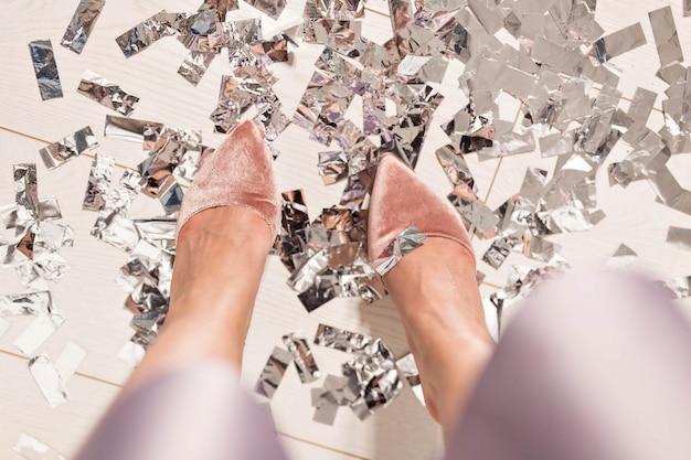 Paar füße bei einer silvester-countdown-party mit konfetti auf dem boden, ansicht von oben.
