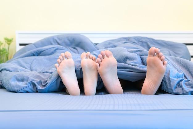 Paar füße von kindern. bruder und schwester liegen unter der decke