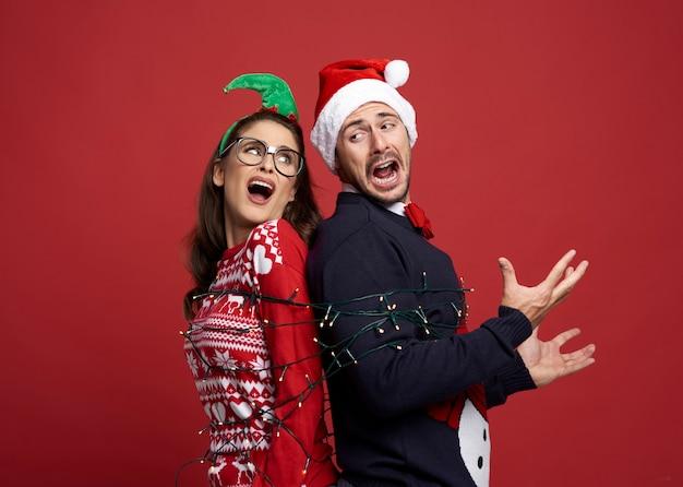 Paar gefangen in der bindung der weihnachtslichter