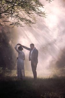 Paar gegen einen weißen nebel im park. schönes paar, das auf dem hintergrund des rauches tanzt
