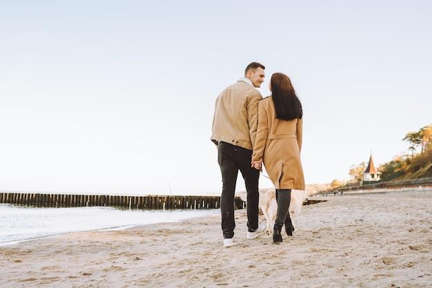 Paar gehen mit ihrem haustier golden retriever am herbsttag am meer spazieren