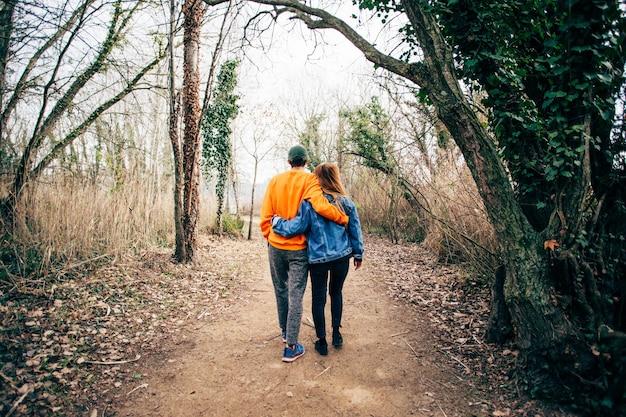 Paar gehen zusammen auf schotterwaldweg