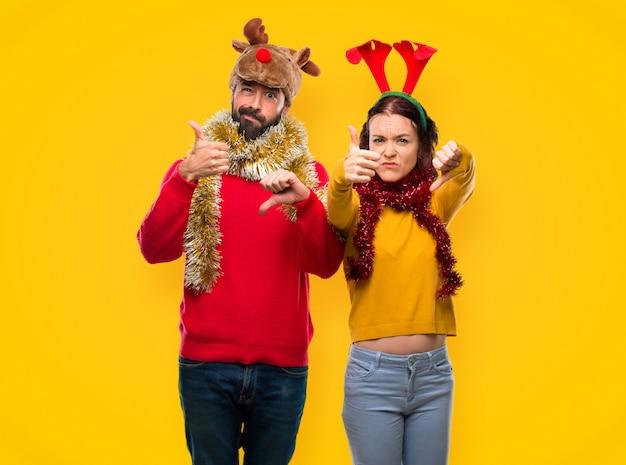 Paar gekleidet für die weihnachtsfeiertage machen gut-schlechtes zeichen. unentschieden zwischen ja o