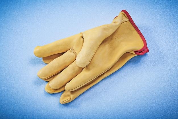 Paar gelbe schutzhandschuhe des leders auf konstruktionskonzept des blauen hintergrunds.