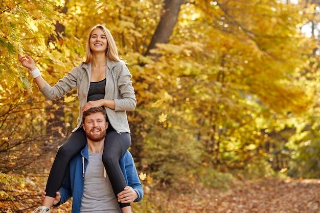 Paar genießen den spaziergang im wald, entzückende junge frau in sportbekleidung sitzen auf dem hals eines freundes oder ehemanns, haben spaß, in betrachtung der natur