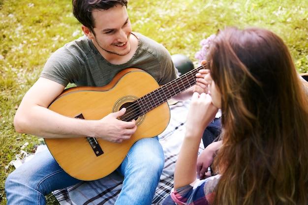 Paar genießt ein picknick im park. mann spielt gitarre. romantisches date