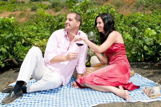 Paar genießt einen tag in den weinbergen und genießt einen guten wein
