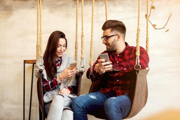 Paar genießt es zu reden und ihre telefone zu benutzen.