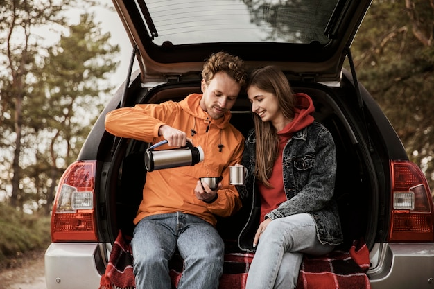Paar genießt heißes getränk während eines road trips