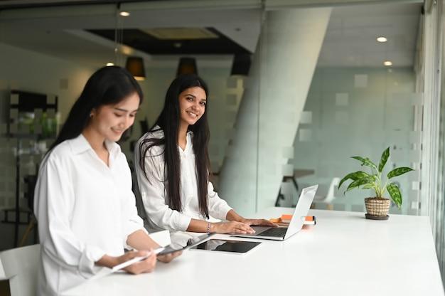 Paar geschäftsleute, die zusammen im modernen büro sitzen und auf dem schreibtisch miteinander sprechen.
