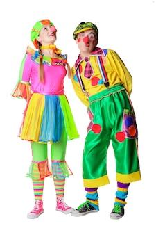 Paar glückliche clowns mit blumen auf weißem hintergrund