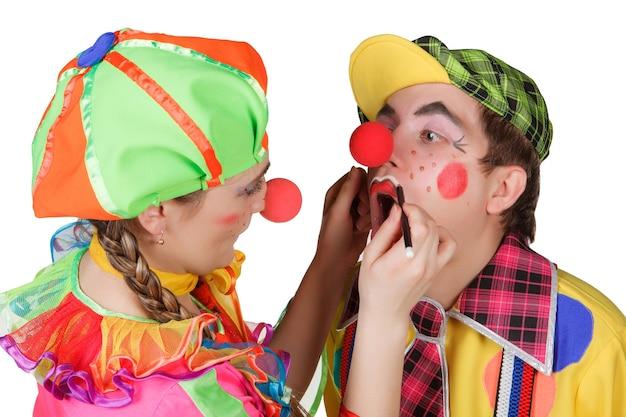 Paar glückliche clowns mit make-up auf weißem hintergrund