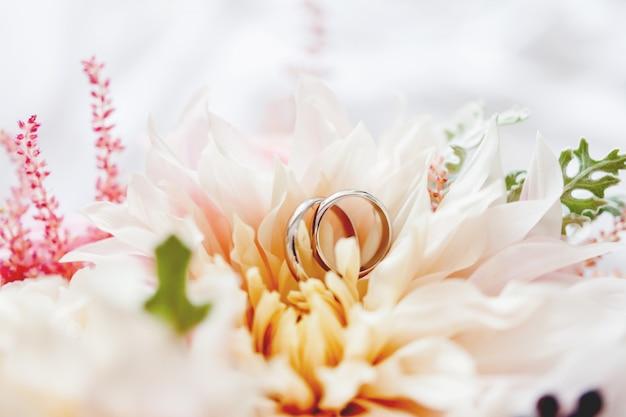 Paar goldene eheringe liegt innerhalb der blume im brautblumenstrauß.