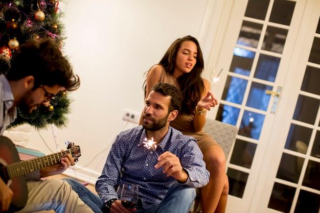 Paar gratuliert neuem jahr mit sprühern während junger mann, der gitarre spielt