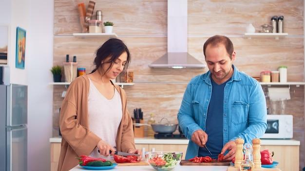 Paar hackt tomaten auf holzbrett für gesunden salat in der küche. kochen, das gesundes bio-lebensmittel glücklich zusammen lebensstil zubereitet. fröhliches essen in der familie mit gemüse