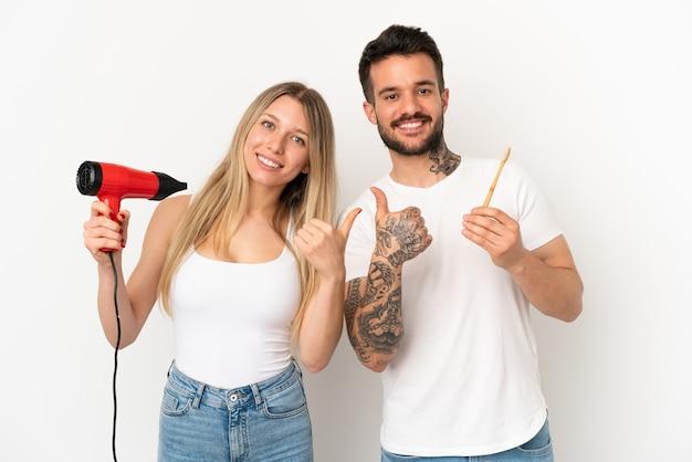 Paar hält einen fön und putzt sich die zähne über isoliertem weißem hintergrund und gibt mit beiden händen eine daumen-hoch-geste und lächelt