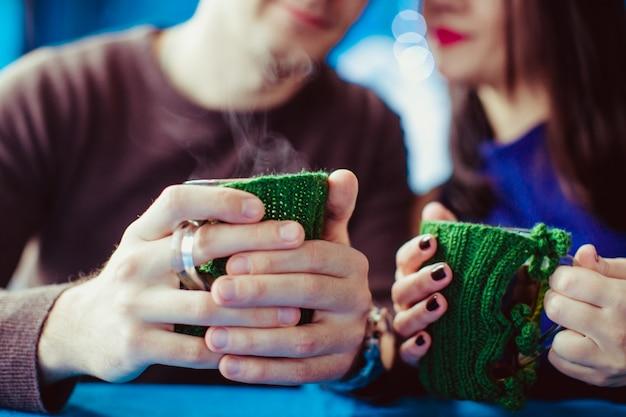 Paar hält gestrickte kaffeetassen in pullover gekleidet