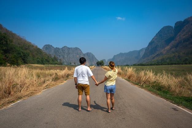 Paar hält hand zusammen auf der straße seitenansicht mit großen schönen felsenbergen uthai thani