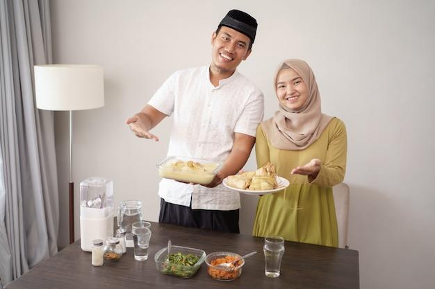 Paar hält opor ayam und ketupat für lebaran