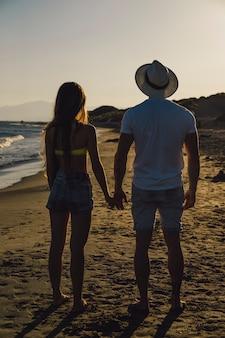 Paar händchen haltend am strand