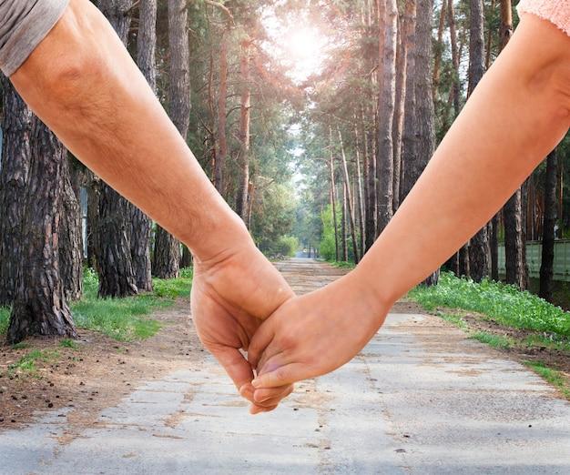 Paar händchen haltend im park