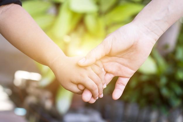 Paar händchenhalten von kind und erwachsenem, um das konzept der menschen zusammenzuhalten