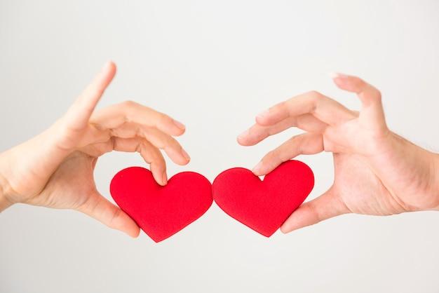 Paar hände halten und stoßen rotes falsches herz lokalisiert auf weißem hintergrund mit kopienraum für text. valentinstag feier. liebe und zusammen konzept.