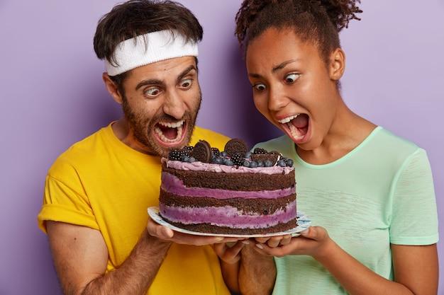 Paar halten den mund weit offen, starren auf leckeren kuchen, fühlen sich versucht, süßes gericht zu essen, tragen lässige t-shirts