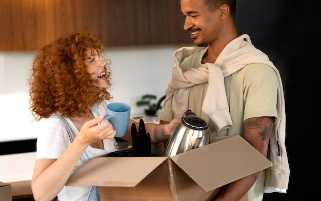 Paar handhabt kartons mit habseligkeiten nach dem zusammenziehen in ein neues zuhause