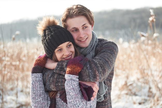 Paar hat spaß und lacht. kuss. junges hipsterpaar, das einander im winterpark umarmt. winterliebesgeschichte, ein schönes stilvolles junges paar. wintermode-konzept mit freund und freundin