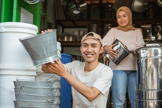Paar haushaltswarenladenbesitzer lächeln, wenn sie nach vorne schauen, während sie den warenbestand im laden überprüfen