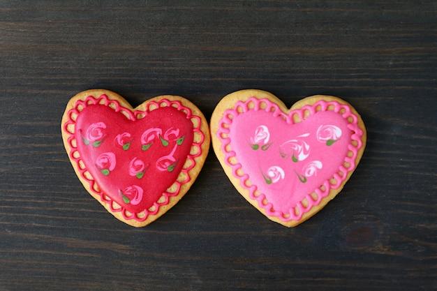 Paar herzförmige blumenmuster royal icing cookies auf schwarzem holzhintergrund isoliert