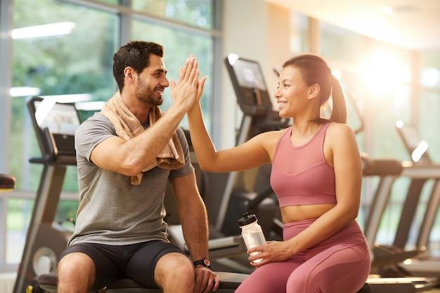Paar high fiving im fitnessstudio