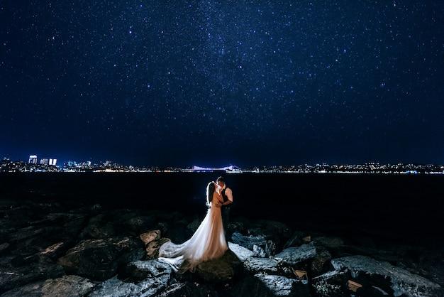 Paar hochzeitssitzung an der küste in der nacht