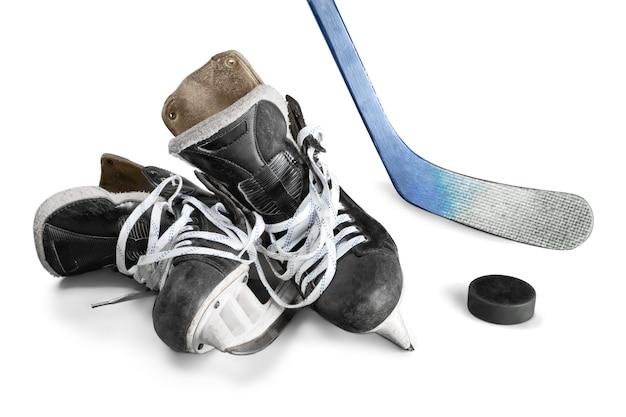 Paar hockeyschlittschuhe mit hockeyschläger und puck isoliert auf weißem hintergrund