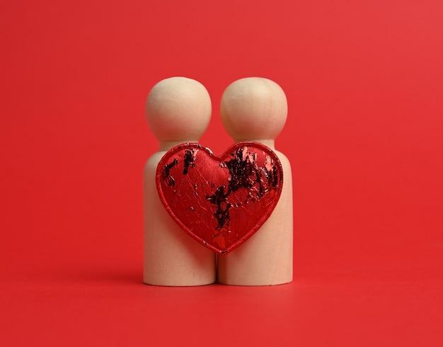 Paar hölzerne männer der braut und des bräutigams, zwischen ihnen ein rotes herz, roter hintergrund, das konzept der liebe und der beziehungen