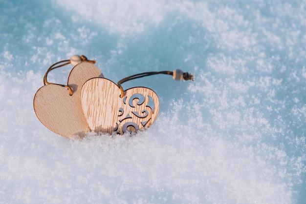 Paar holzherzen im kalten, frostigen morgenschnee. valentinstag grußkarte. symbol der liebe