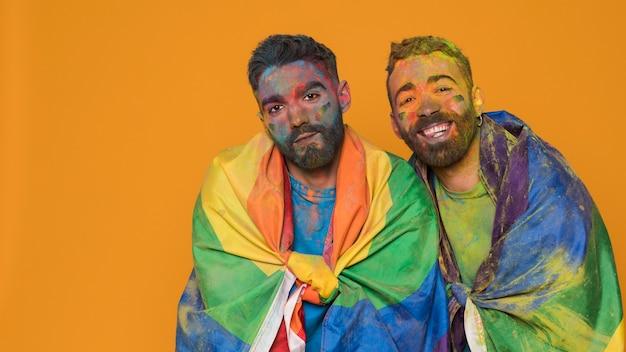 Paar homosexuelle männer in der kunstfarbe bedeckt durch lgbt-flagge