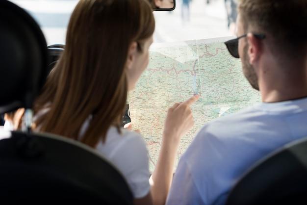 Paar im auto, das karte betrachtet