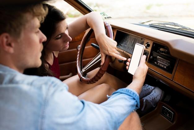 Paar im auto mit blick auf smartphone