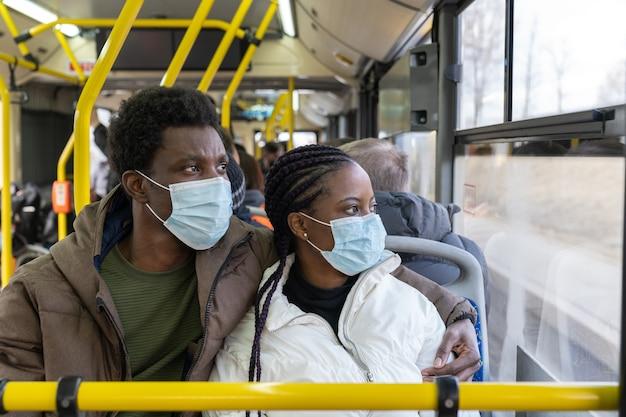 Paar im bus, der masken trägt, während er in neuen normalen afrikanischen männern und frauen in öffentlichen verkehrsmitteln reist