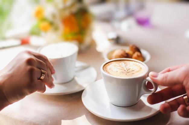 Paar im café, eine tasse kaffee haltend