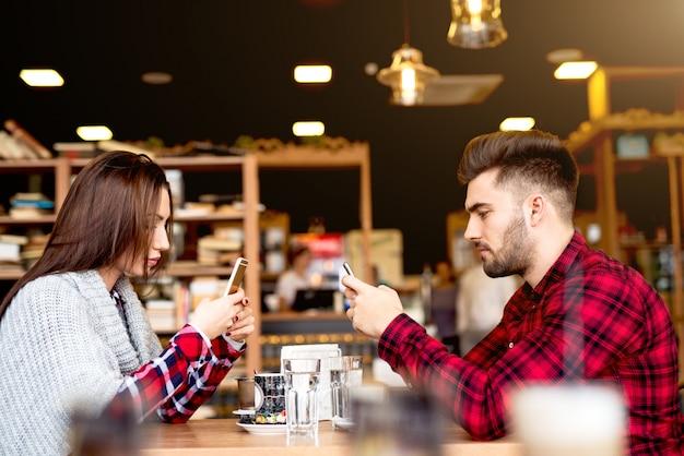 Paar im café mit ihren telefonen.