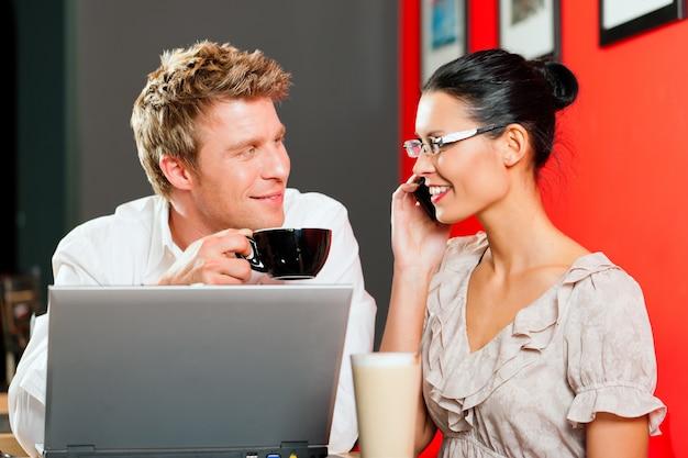 Paar im coffeeshop mit laptop und handy